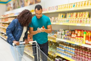 couple choosing canned goods in the grocery store