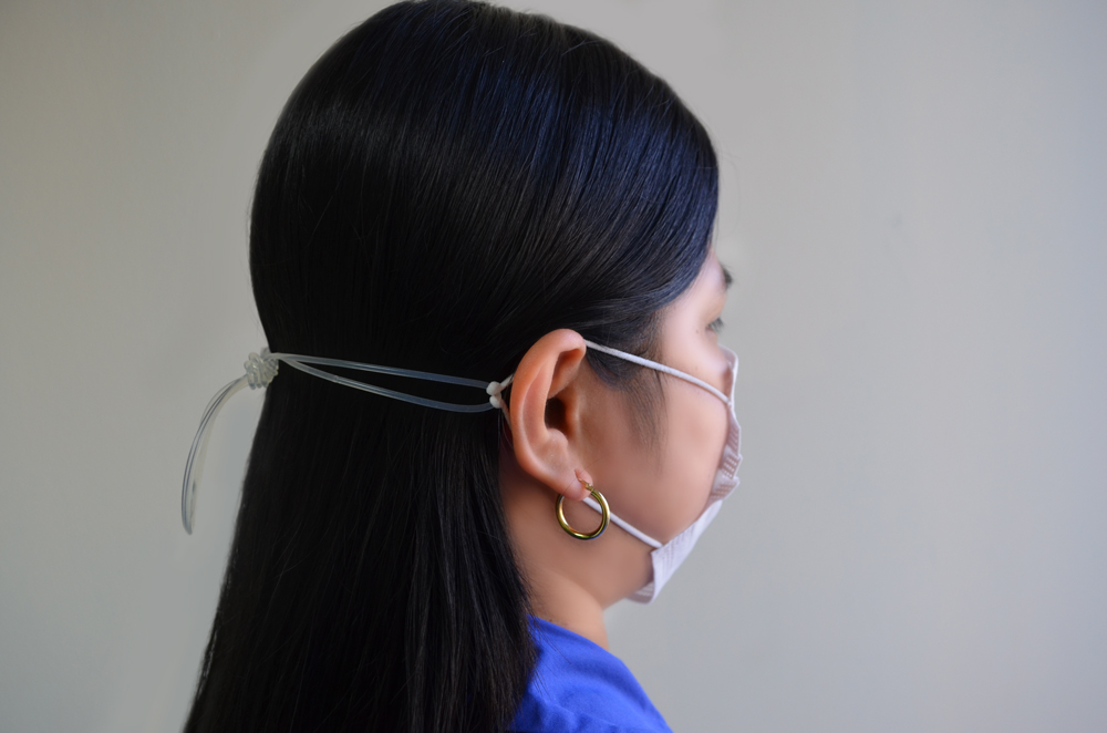 Woman wearing surgical mask with string tied at the back of her head