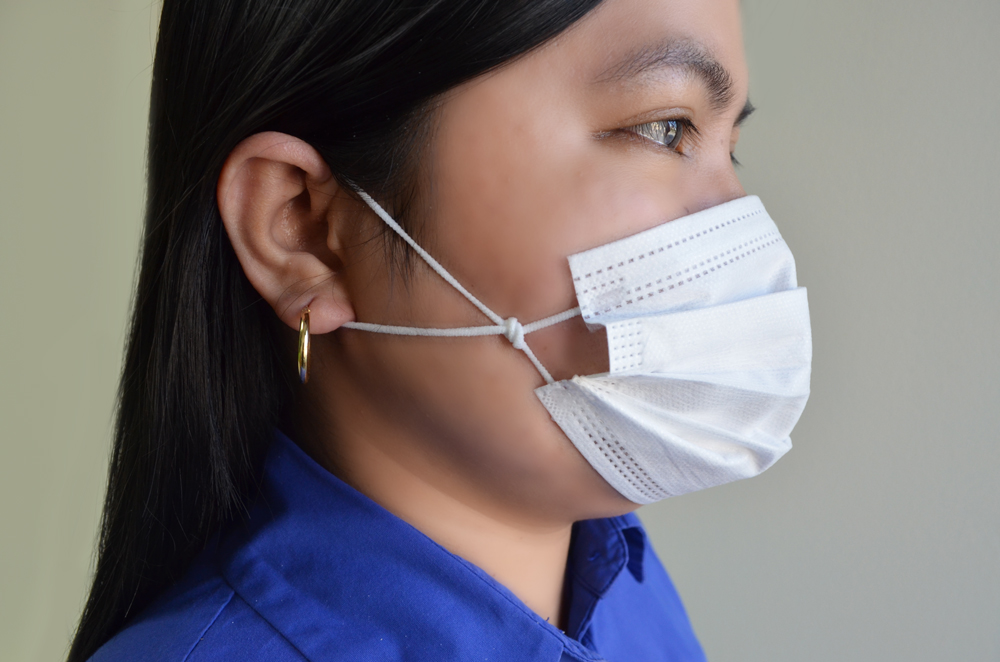 Woman wearing surgical mask with knotted ear loops